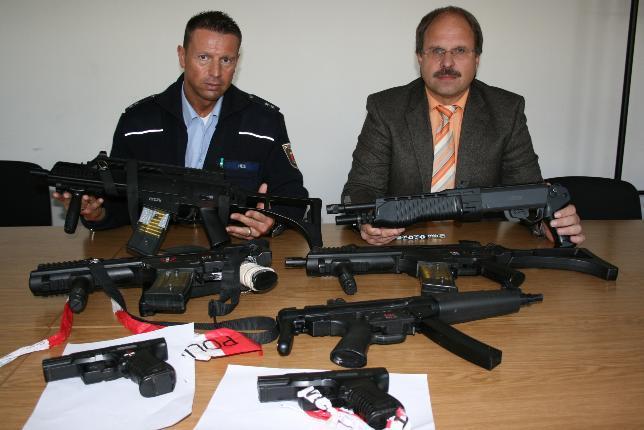 Timo Heß (li.) und Achim Reimann von der Polizeiinspektion Kirn demonstrieren die sogenannten Anscheinswaffen, die unlängst bei einem Einsatz in der VG Bad Sobernheim sichergestellt wurden und sich als Softair-Waffen herausgestellt haben.