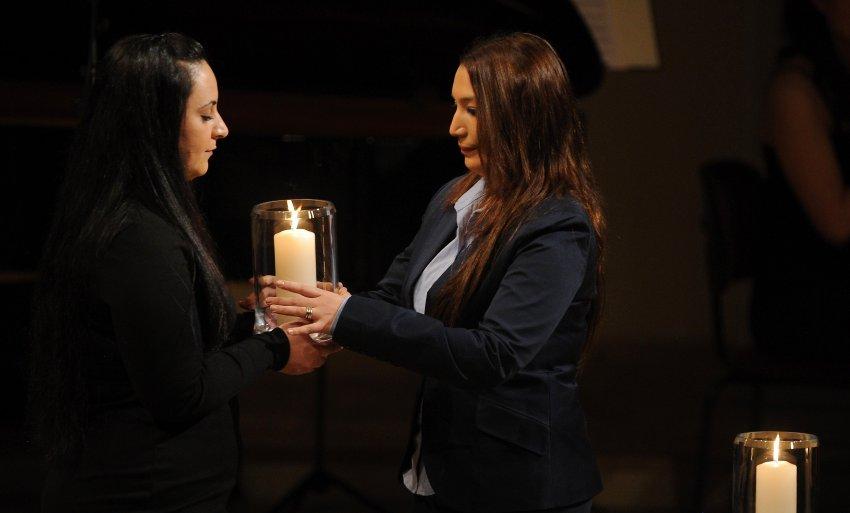 Semiya Simsek (r) und Gamze Kubasik tragen während der Gedenkveranstaltung für die Opfer rechtsextremistischer Gewalt am Donnerstag (23.02.2012) im Konzerthaus in Berlin eine Kerze. Zeitgleich sollen mit bundesweiten Schweigeminuten die zehn Menschen geehrt werden, die zwischen 2000 bis 2006 von Mitgliedern einer Neonazi-Zelle getötet wurden. Foto: Hannibal dpa/lbn +++(c) dpa - Bildfunk+++
