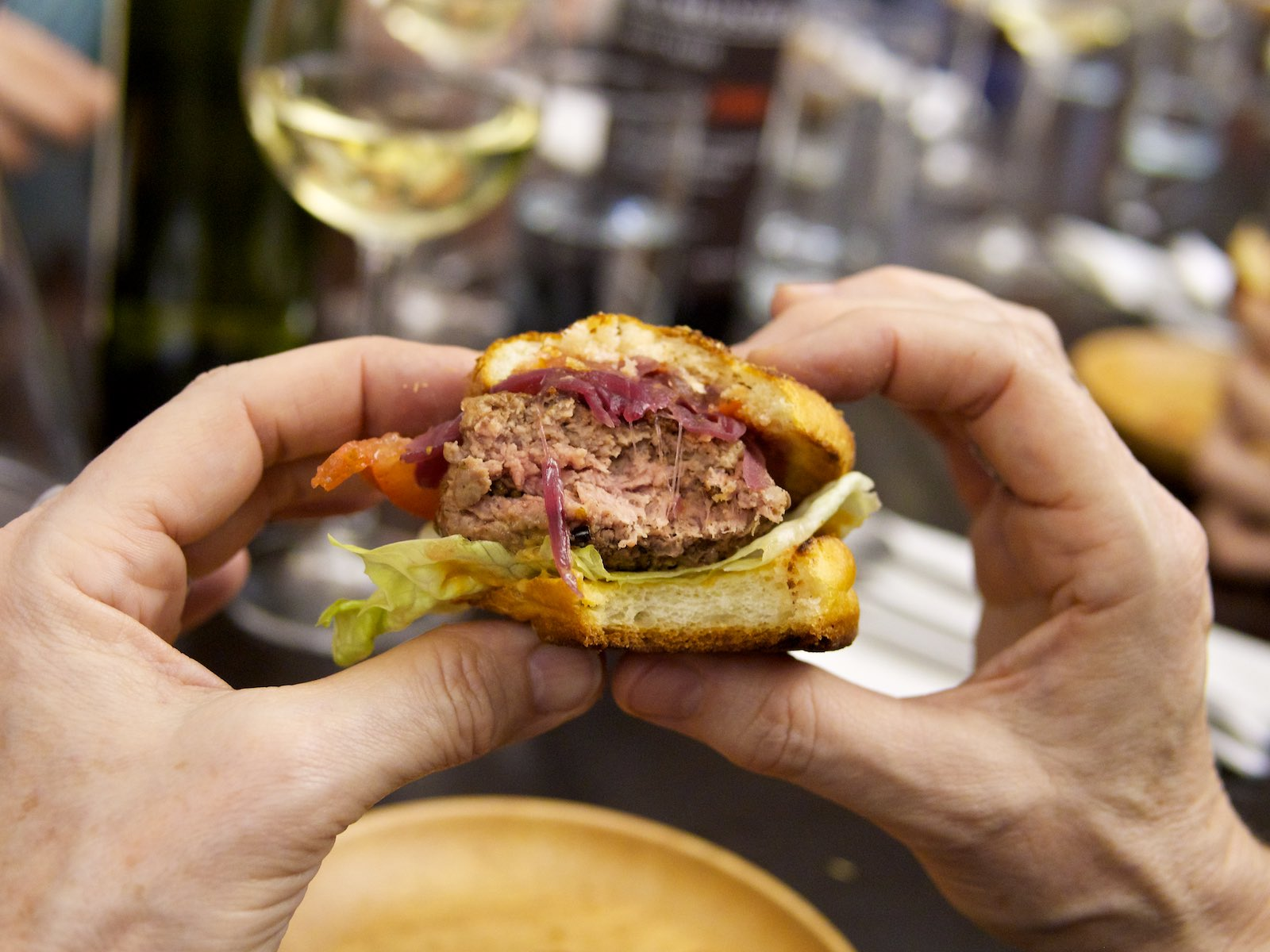 Ein angebissener Briocheburger mit Rindfleisch-Grille-Heimchen-Laberl und Mehlwurm-Knusper