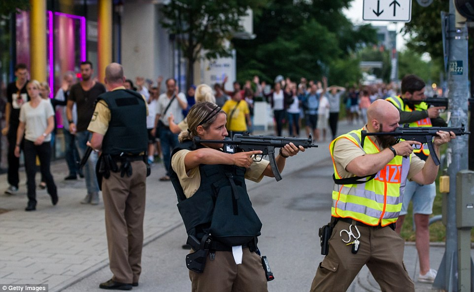 3683263F00000578-3703705-Police_officers_guard_with_guns_as_other_officers_escort_people_-a-12_1469227700673